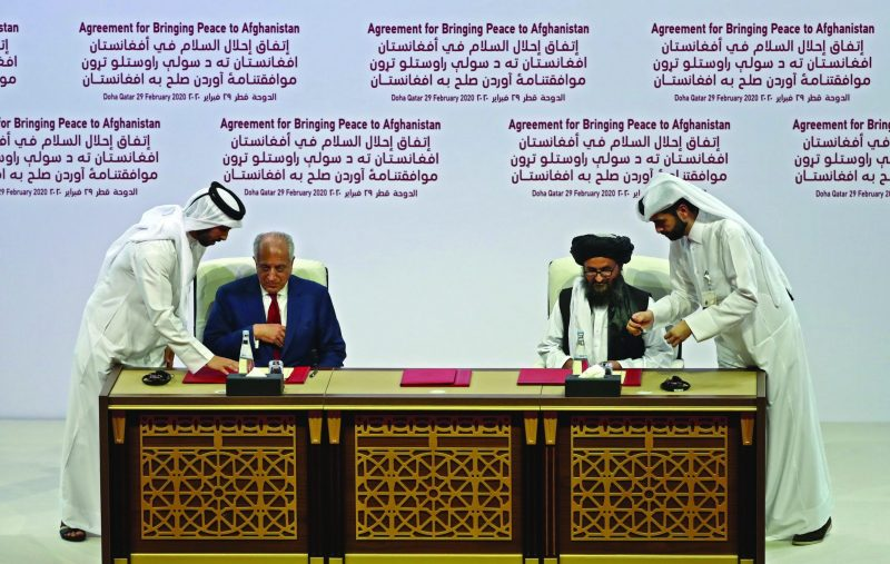 (L to R) US Special Representative for Afghanistan Reconciliation Zalmay Khalilzad and Taliban co-founder Mullah Abdul Ghani Baradar sign the US-Taliban peace agreement during a ceremony in the Qatari capital Doha on February 29, 2020. - The United States is signed a landmark deal with the Taliban, laying out a timetable for a full troop withdrawal from Afghanistan within 14 months as it seeks an exit from its longest-ever war. (Photo by KARIM JAAFAR / AFP)