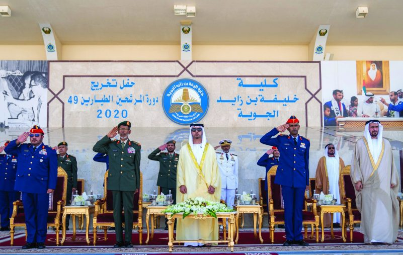 AL AIN, ABU DHABI, UNITED ARAB EMIRATES - March 01, 2020: HH Sheikh Hazza bin Zayed Al Nahyan, Vice Chairman of the Abu Dhabi Executive Council (3rd L), stands for the national anthem during the Khalifa bin Zayed Air College graduation ceremony. Seen with HE Major General Ibrahim Nasser Al Alawi, Commander of the UAE Air Forces and Air Defence (L) and HE Lt General Hamad Thani Al Romaithi, Chief of Staff UAE Armed Forces (2nd L)  ( Hamad Al Kaabi  / Ministry of Presidential Affairs ) ---